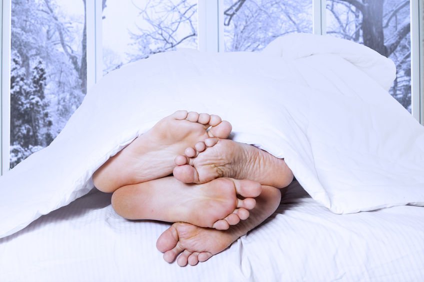 33787429 - affectionate of couple sleeping on the bedroom looks from their feet, shot in winter day