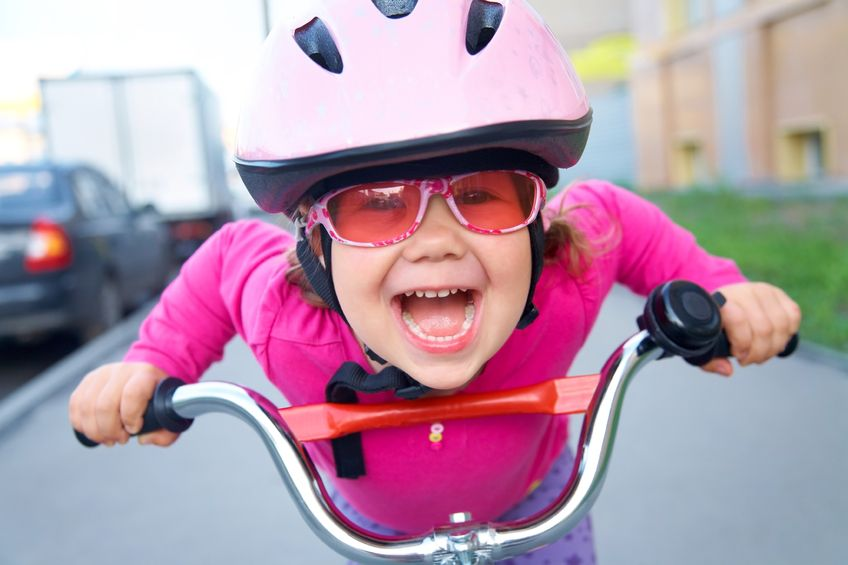 10229030 - portrait of a playful funny girl in a pink safety helmet on her bike