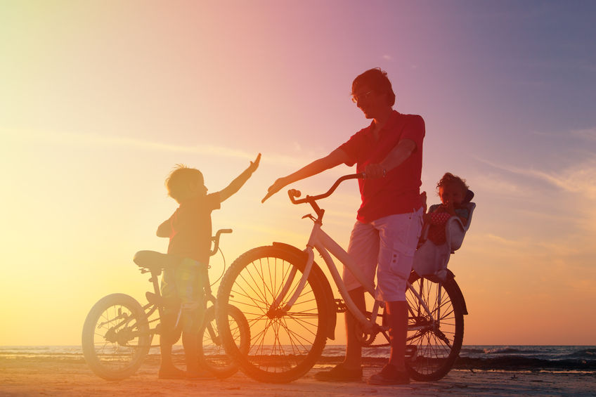 45128165 - silhouette of father with two kids on bikes at sunset
