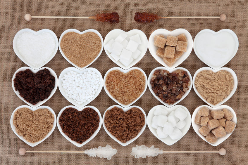 35089428 - white and brown sugar selection in heart shaped bowls with crystal lollipop sticks over hessian background.